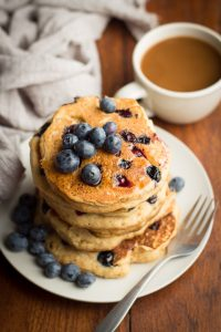 Blueberry Cornbread Pancakes on a Plate with Coffee Cup in the Background