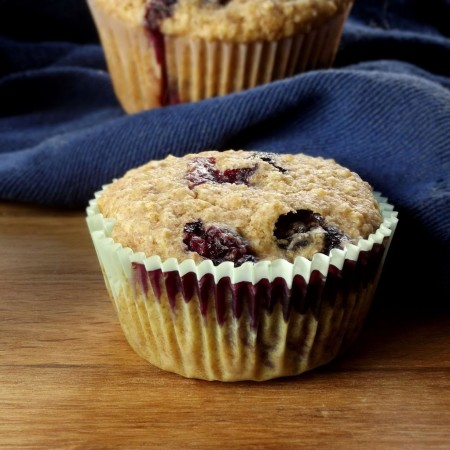 Close Up of a Blueberry Quinoa Muffin with Blue Napkin in the Background