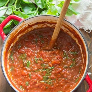 Pot of Marinara Sauce with a Bunch of Basil on the Side