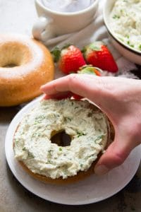 Hand Grabbing a Cashew Cream Cheese Topped Bagel From a Plate
