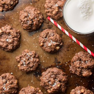 Overhead View of Vegan Chocolate Cookies and Glass of Almond Milk on a Baking Sheet