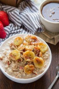 A Bowl of Caramelized Banana Oatmeal with Coffee Cup and Strawberries in the Background