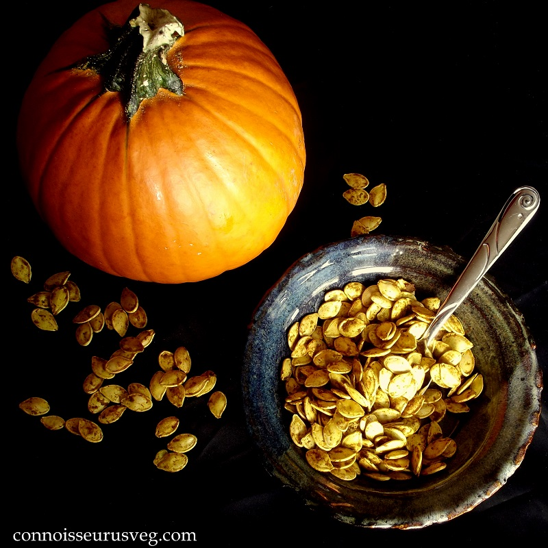 Overhead View of a Dish of Pumpkin Seeds with Spoon and Pumpkin on a Black Surface