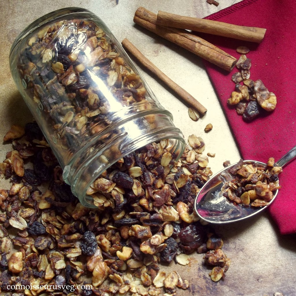 Jar of Granola Spilling on a Distressed Surface with Spoon and Cinnamon Sticks