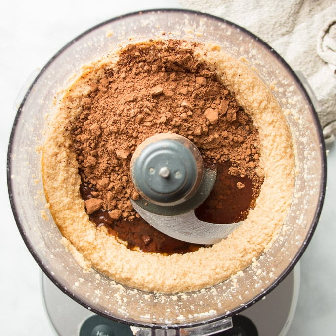 Blended Hazelnuts in a Food Processor Bowl with Cocoa Powder, Maple Syrup, Vanilla and Salt