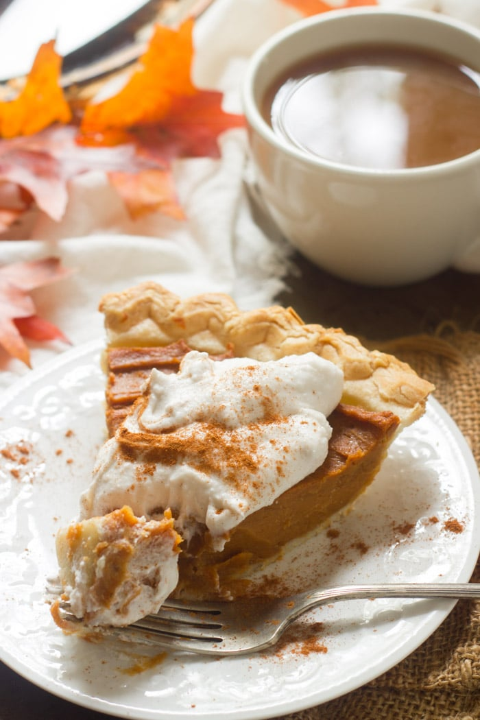 Chai-Spiced Vegan Sweet Potato Pie on a Plate with Fork and Coconut Whipped Cream