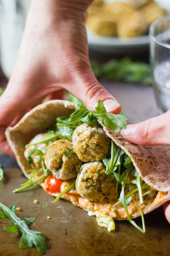 Pair of Hands Picking Up a Baked Quinoa Falafel Sandwich