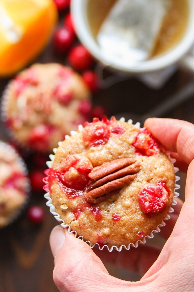 Close Up of a Hand Holding a Cranberry Orange Quinoa Muffin