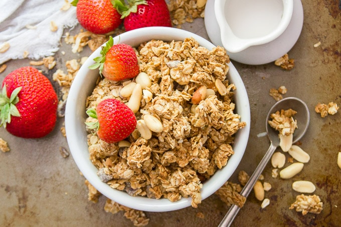 Overhead View of a Bowl of Peanut Butter Granola and Strawberries with Spoon on the Side