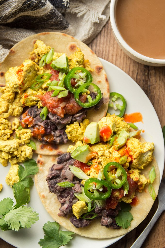 Close Up of Two Vegan Huevos Rancheros Topped with Salsa and Jalapeno Peppers