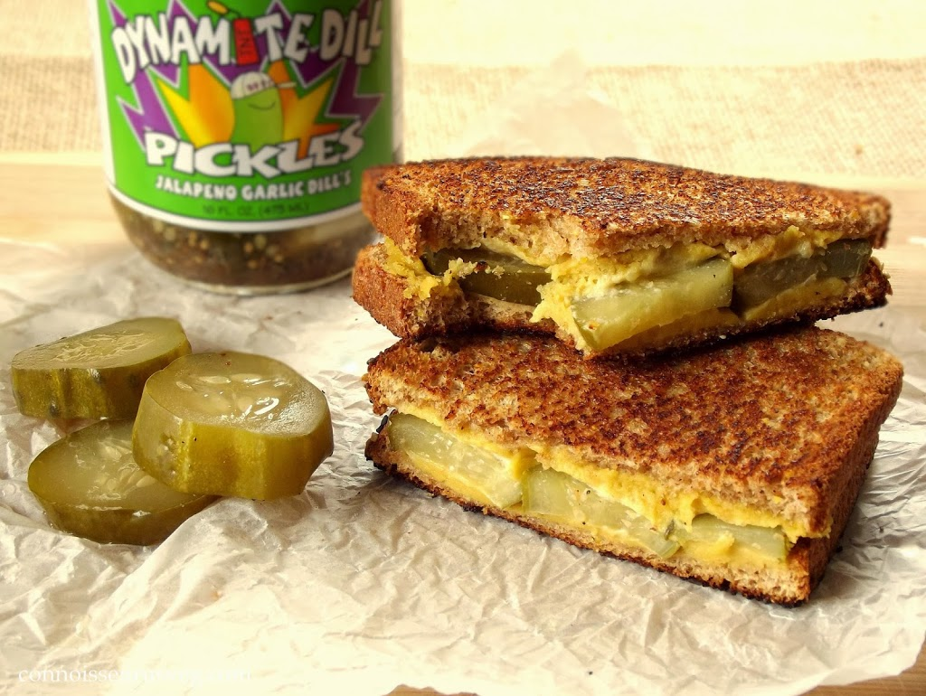 Two Halves of a Dill Pickle Grille Cheese Sandwich with Pickle Jar in the Background