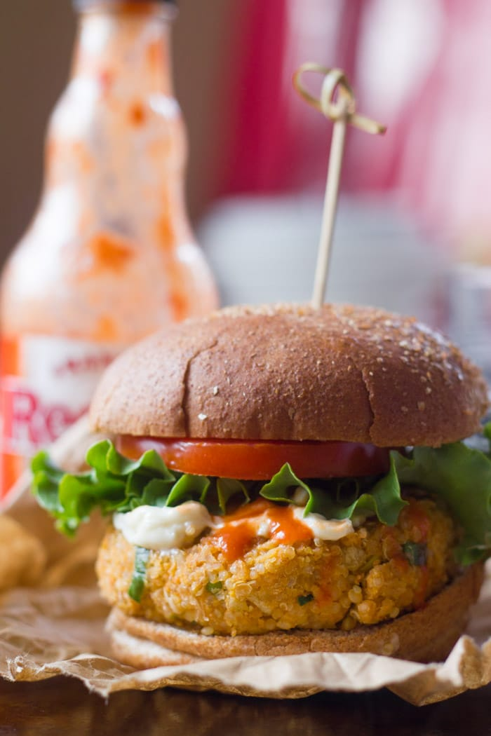 Buffalo Chickpea Quinoa Burger with a Bottle of Hot Sauce in the Background
