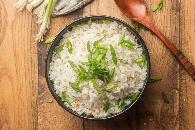 Bowl of Coconut Rice Topped with Scallions and Sesame Seeds on a Wooden Surface