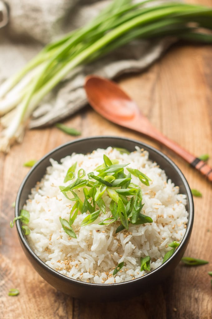 Bowl of Coconut Rice with Bunch of Scallions and Wooden Spoon in the Background