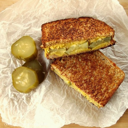 Two Halves of a Dill Pickle Grilled Cheese Sandwich and a Pickle, Cut in Half