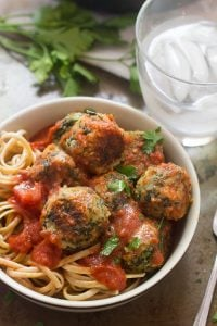Bowl of Cannellini Bean & Broccoli Rabe Meatballs Over Linguine with Water Glass in the Background