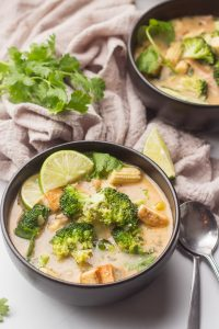 Two Bowls of Thai Coconut Soup with Napkin, Lime Wedge, and a Bunch of Cilantro