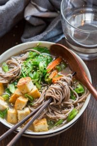 Close Up of a Bowl of Miso Soba Noodle Soup with Crispy Tofu with Wooden Soon and Noodles Wrapped Around Chopsticks