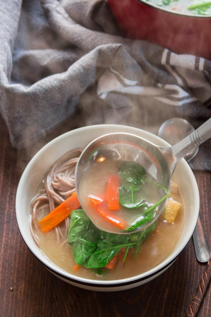 Ladle Pouring Miso Soba Noodle Soup into a Bolw