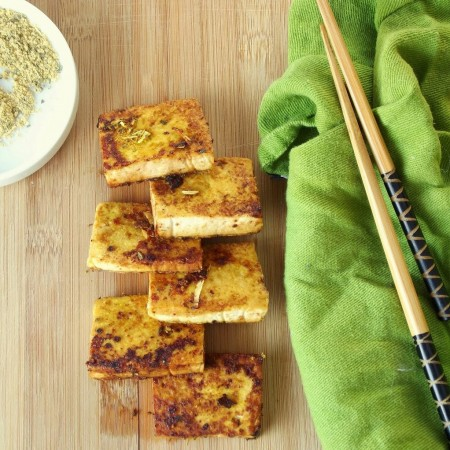 Tofu Squares on a Wooden Surface with Green Napkin and Chopsticks on the Side