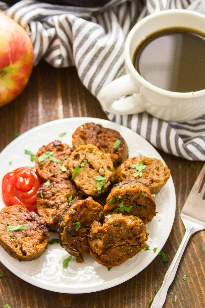 Vegan Breakfast Sausage on a Plate with Coffee Cup and Apple in the Background