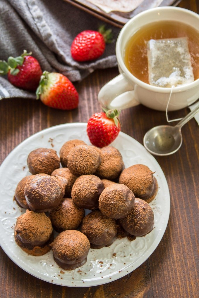 Plate of Vegan Truffles with Strawberries and a Cup of Tea in the Background