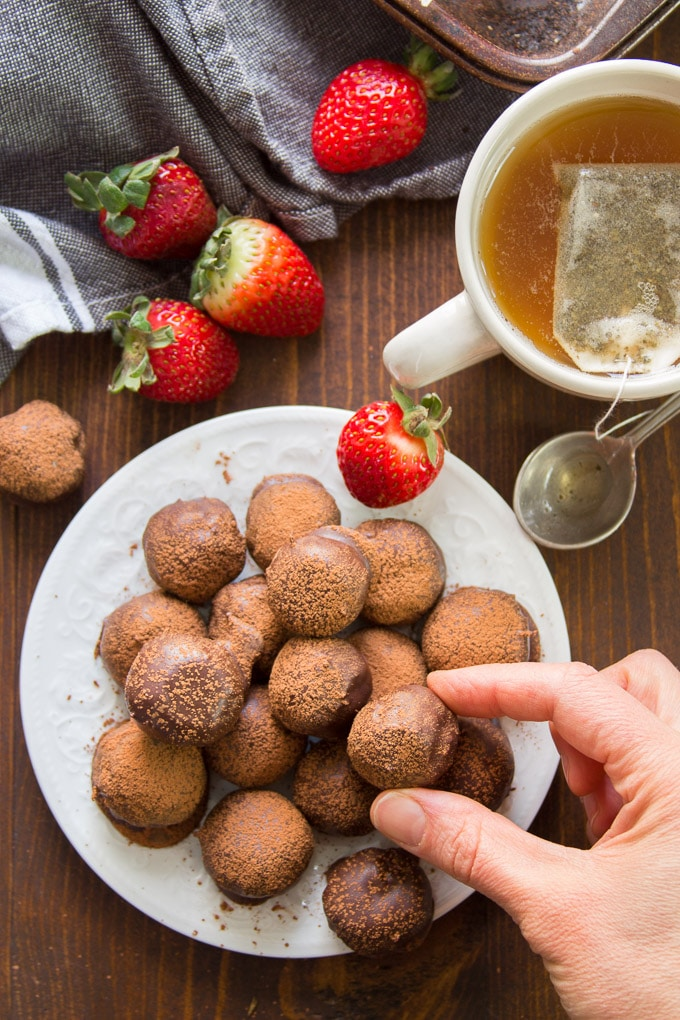 Hand Grabbing a Vegan Truffle From a Plate