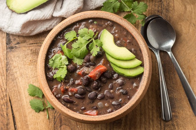 Bowl of Spicy Black Bean Soup Topped with Avocado and Cilantro on a Wooden Table