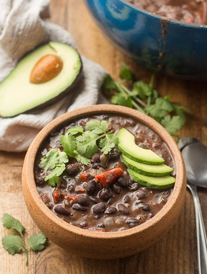 Spicy Black Bean Soup with Pot, Cilantro, Napkin and Avocado Half in the Background