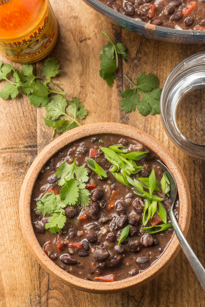 Bowl of Spicy Black Bean Soup With Cilantro and Scallions, Water Glass and a Bottle of Hot Sauce on a Wooden Table