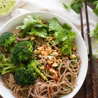 Bowl of Cilantro Peanut Soba Noodles and Broccoli on a Distressed Surface with Cloth and Chopsticks