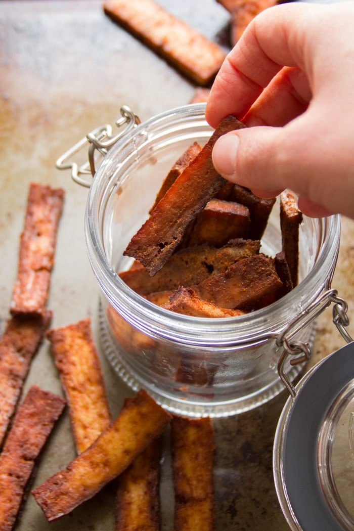 Hand Removing a Piece of Tofu Jerky from a Jar