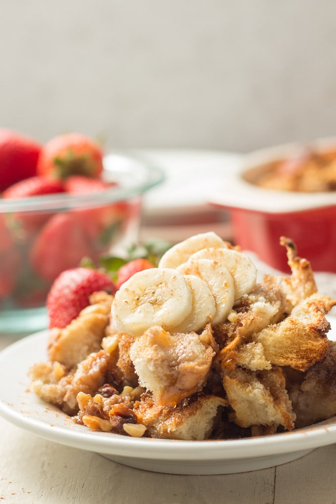 Close Up of a Piece of Vegan French Toast Casserole with Bowl of Strawberries and Casserole Dish in the Background
