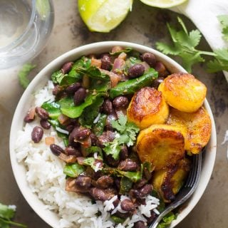 Black Beans and Rice with Collard Greens and Pan-Fried Plantains in a Bowl on a Rustic Surface