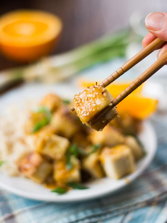 Close Up of a Piece of Crispy Orange Ginger Tofu Being Gripped by Chopsticks