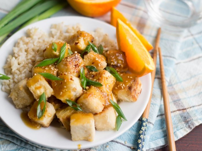 Crispy Orange Ginger Tofu on A Plate with Scallions and Orange Slices in the Background