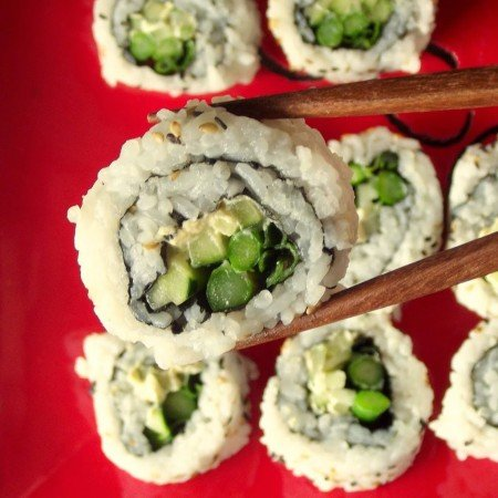 Close Up of a Pair of Chopsticks Holding a Piece of Veggie Sushi Over a Red Plate