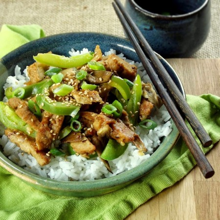 Sesame Seitan and Peppers Over Rice on a Plate with Chopsticks Perched on the Side