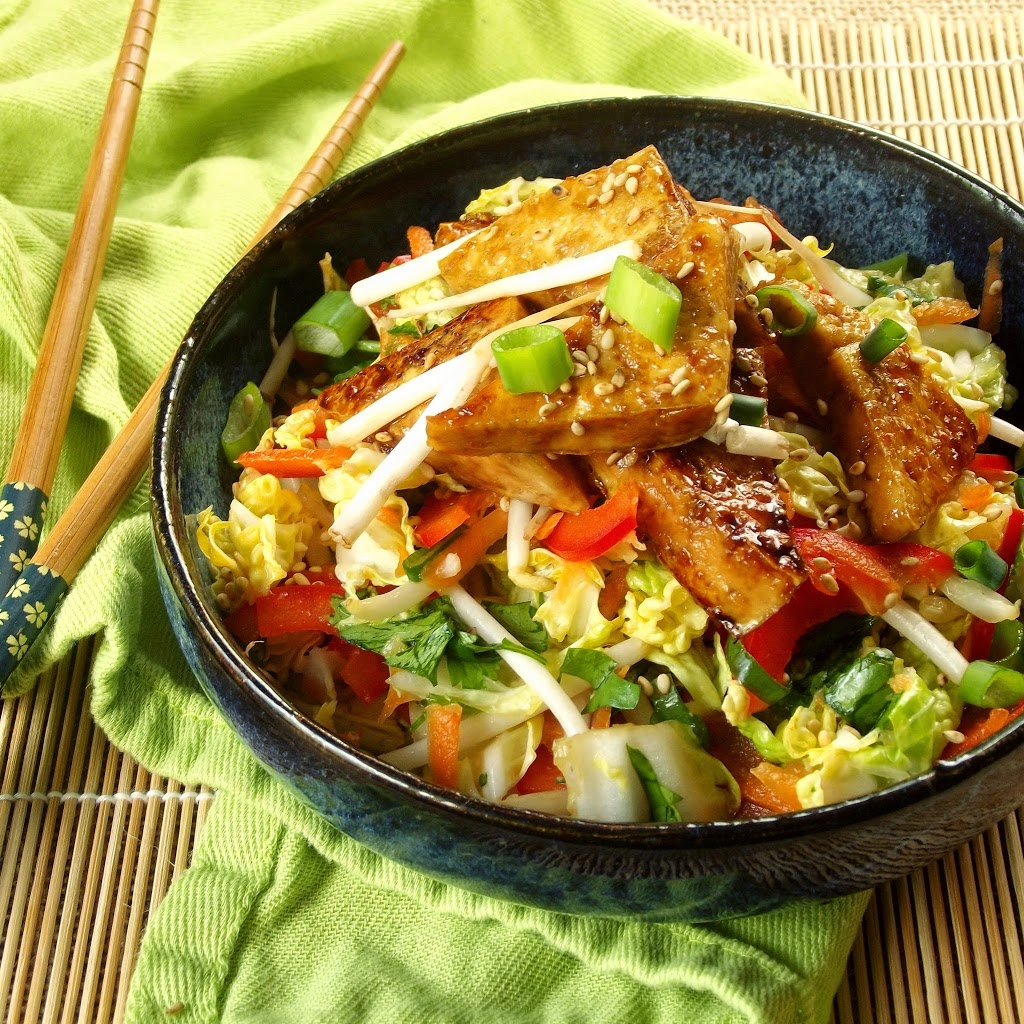 Bowl of Sticky Tofu Over Slaw Sitting on a Green Cloth with Chopsticks on the Side