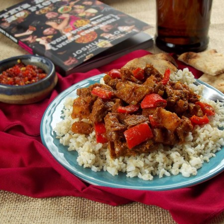 Plate of Vegan Vindaloo on a Plate Over Rice with Cookbook and Beer Bottle in the Background