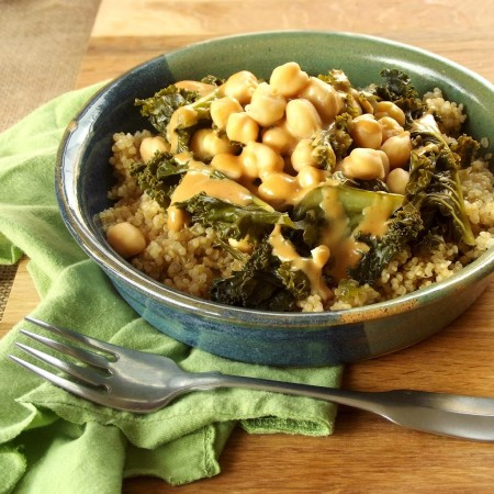 Bowl of Chickpeas, Kale and Tahini Dressing Over Quinoa on a Green Cloth, Fork in Front
