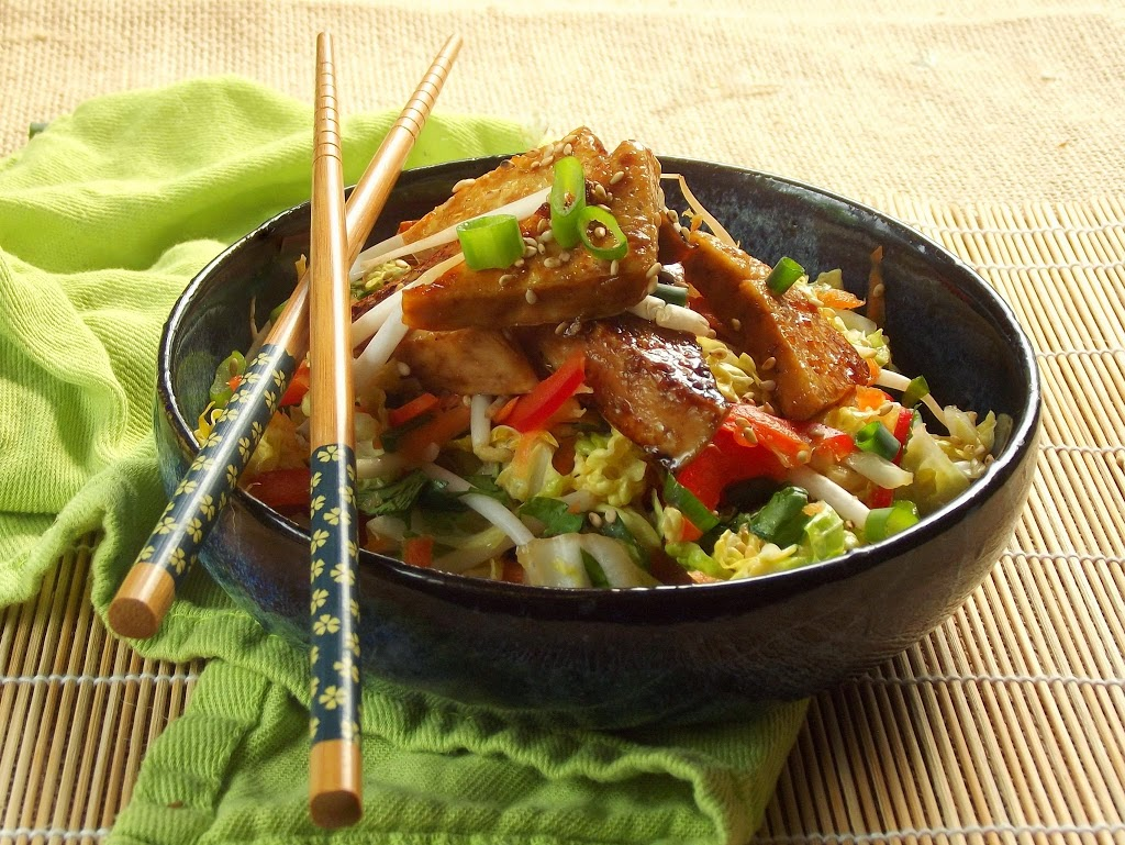 Bowl of Sticky Tofu and Slaw with Chopsticks Perched on the Side