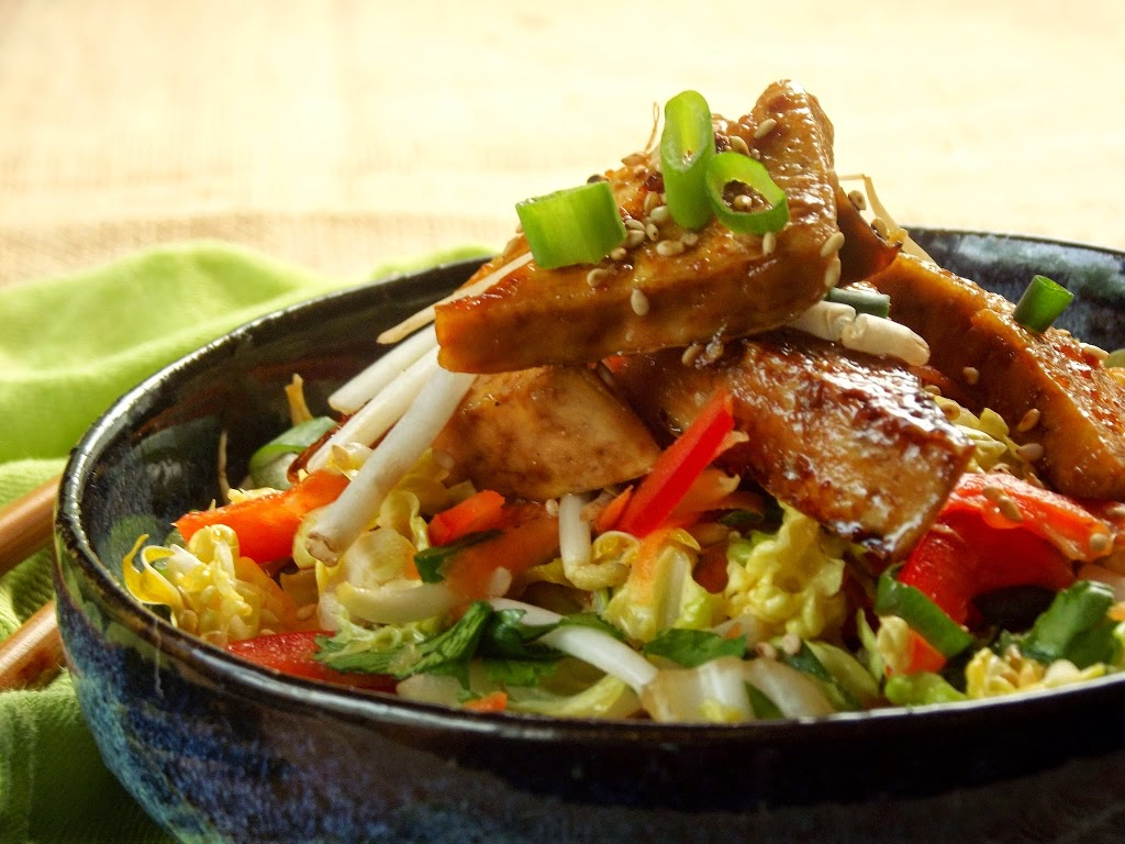 Close Up of Sticky Tofu Triangles Piled Over a Bowl of Slaw