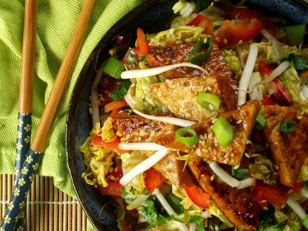 A dish is filled with food, with Tofu and Coleslaw
