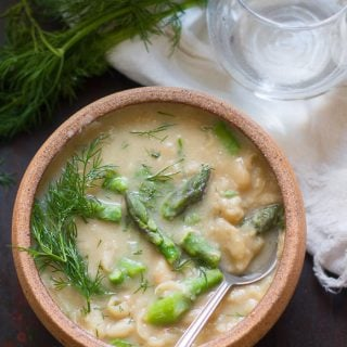 Bowl of Creamy White Bean Asparagus & Dill Soup and Spoon on a Distressed Surface with Fresh Dill and Water Glass
