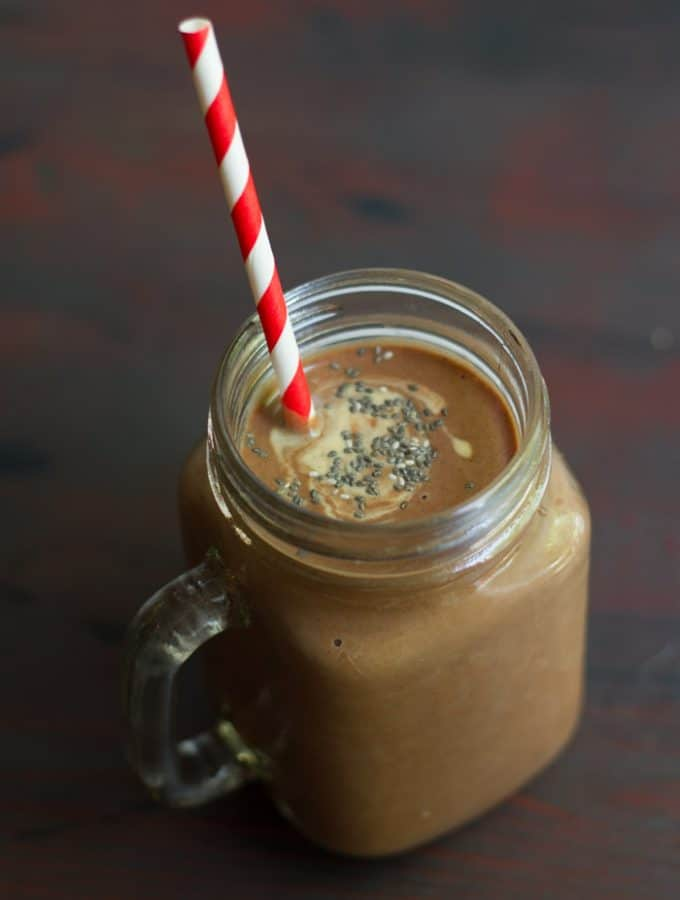 Glass Filled with Chocolate Peanut Butter Chia Smoothie with a Striped Straw and Topped with Chia Seeds