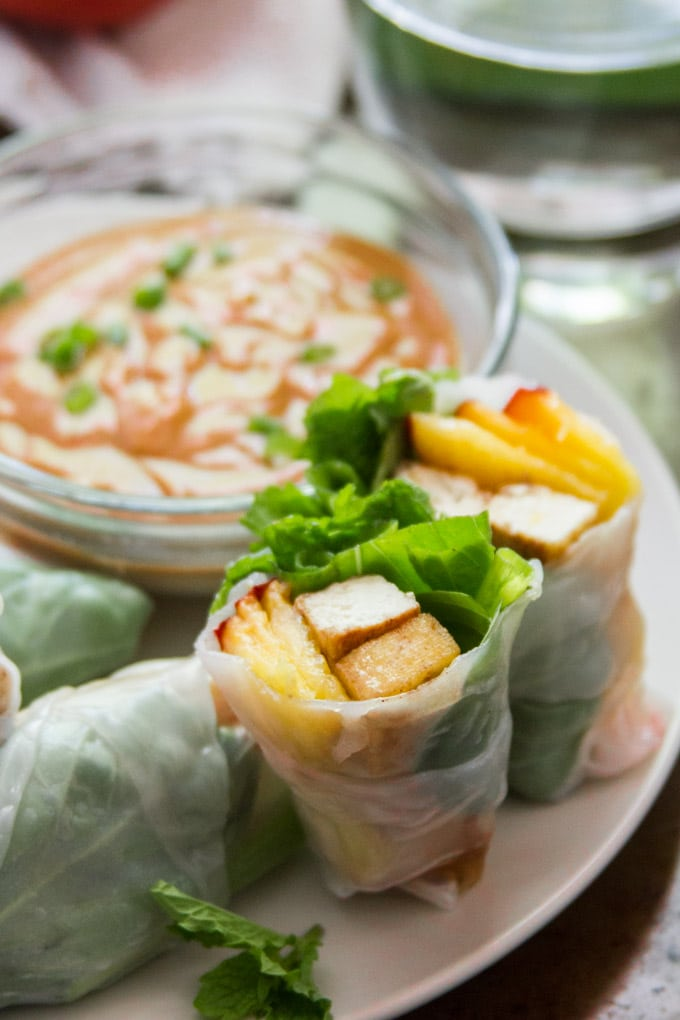 A Halved Tofu & Peach Summer Roll on a Plate with a Bowl of Peanut Sauce