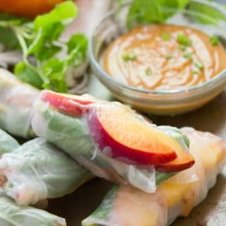 Tofu & Peach Summer Rolls with Peanut Dipping Sauce with Peanut Sauce, Fresh Herbs and Peaches in the Background