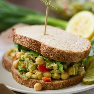 Chickpea Sandwich on a Plate with Scallions and Lemon Half in the Background