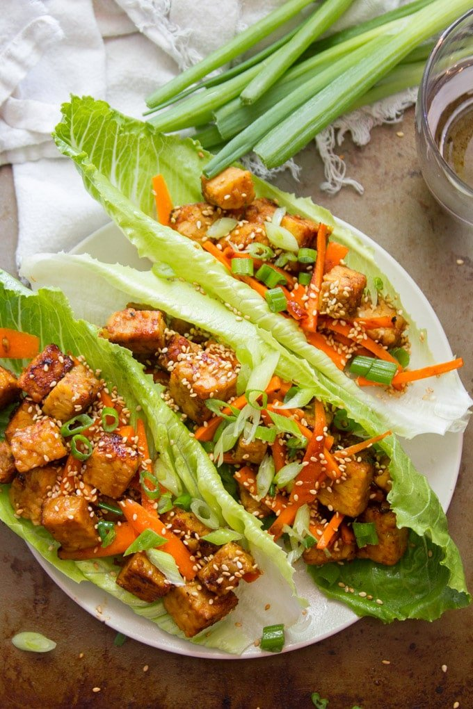 Overhead View of Three Ginger Sesame Tempeh Vegan Lettuce Wraps with Napkin, Drinking Glass, and a Bunch of Scallions